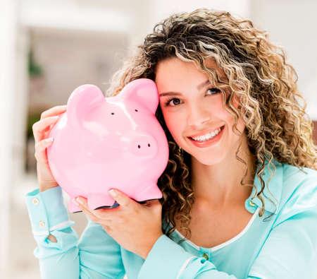 coinbank: Mujer sosteniendo una hucha y mirando muy feliz Foto de archivo