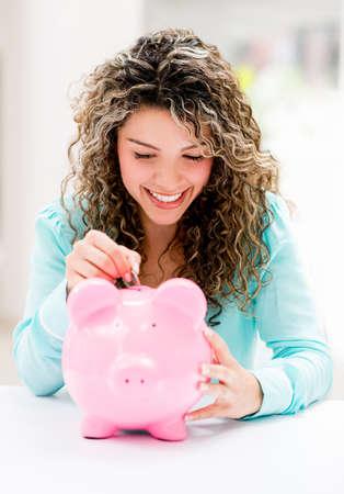 coinbank: Mujer feliz que pone ahorros en una hucha