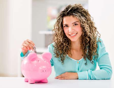 coinbank: Feliz ahorrar dinero en una alcanc�a Mujer Foto de archivo