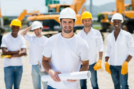Architect with a group at a construction site holding blueprints photo
