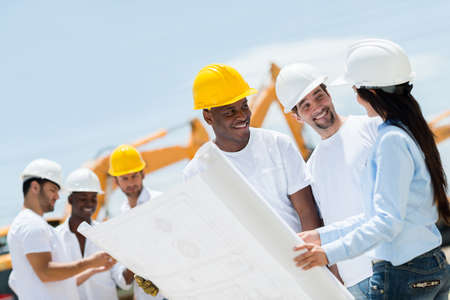 Architect at a construction site looking at blueprints with workers photo
