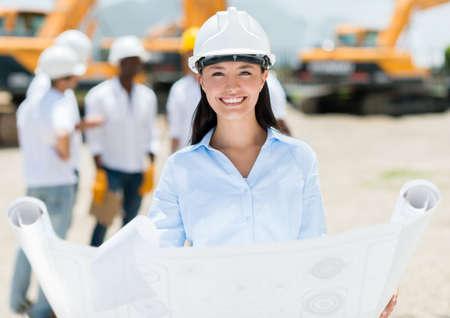 arquitecto: Arquitecto femenina en un sitio de construcci?n, celebraci?n de planos