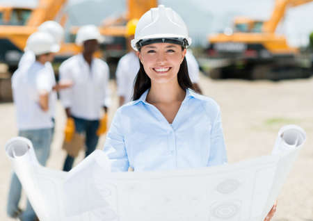 Female architect at a construction site holding blueprints photo
