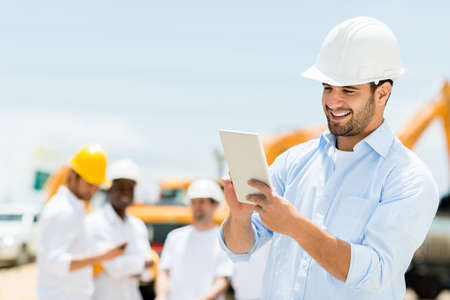 Male engineer at a construction site with a tablet computer photo