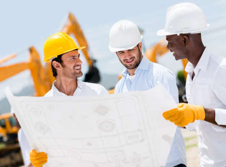 Group of architects at a construction site looking at blueprints Stock Photo - 21467346