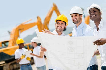 Gruppe der Arbeiter auf einer Baustelle halten Blaupausen