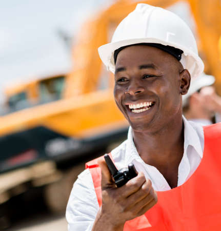 Construction worker with a walkie-talkie looking very happy photo