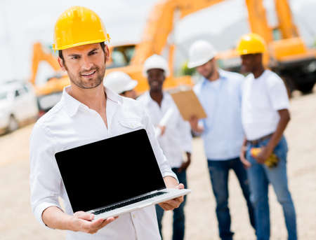 Male construction worker with a laptop computer photo