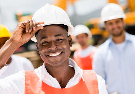 civil engineer: Happy construction worker at a building site wearing a helmet Stock Photo