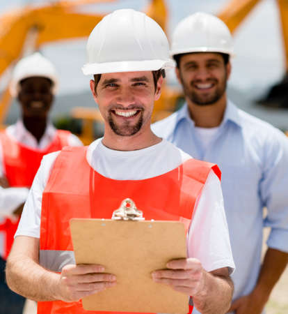 Happy construction worker holding a clipboard and smiling photo
