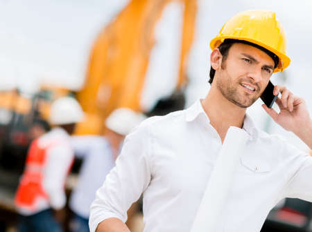 engineers: Engineer talking on the phone on a construction site Stock Photo