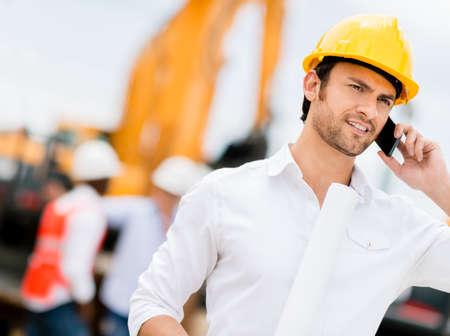 ingeniero civil: Ingeniero de hablar por tel�fono en un sitio de construcci�n