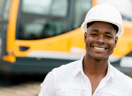 constructors: Construction worker with machines at the background looking happy Stock Photo