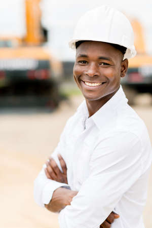 Architect at a construction site wearing a helmet and smiling photo