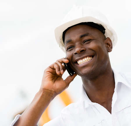 Architect talking on the phone at a construction site photo