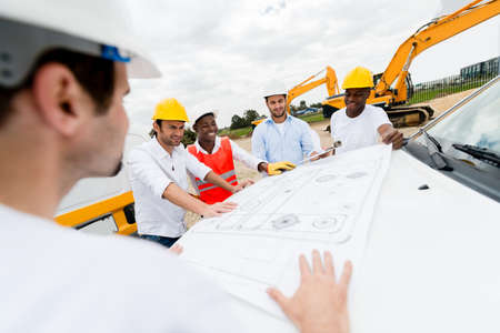 Group of architects looking at blueprints at a construction site Stock Photo - 21467366
