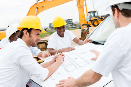 Group of civil engineers working on a construction and looking at blueprints Stock Photo - 21467369