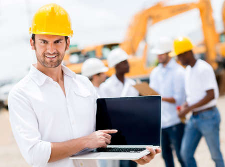 Architect with laptop computer at a building site