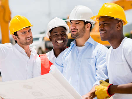 construction plan: Architect at a building site looking at blueprints with a group of workers