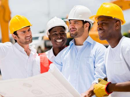 ingeniero civil: Arquitectos en un sitio de construcci�n mirando planos con un grupo de trabajadores