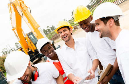 Happy group of workers laughing at a building site