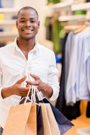 Happy shopping man holding bags at the mall Stock Photo - 21467390