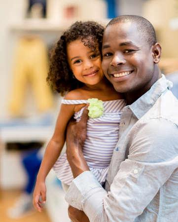 ni�os negros: Hermoso retrato de un padre y su hija de compras para la ropa Foto de archivo