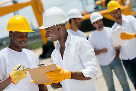 engineering clipboard: Happy architects working at a construction site outdoors