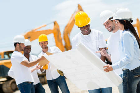 construction project: Group of architects at a construction site looking at blueprints