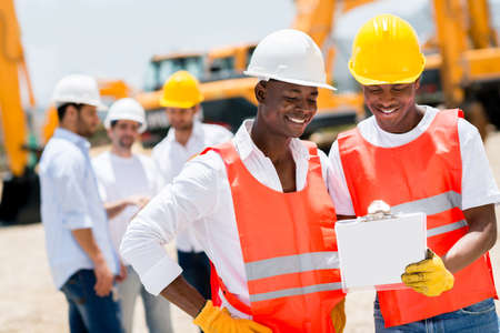 Team of male workers at a building site looking happy Stock Photo