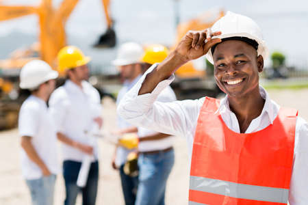 Happy male architect at a building site wearing a helmet photo