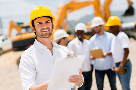 Male architect at a building site holding clipboard photo