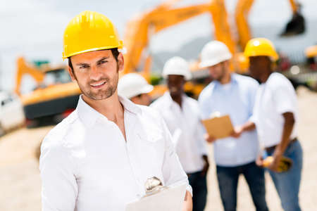 Handsome male engineer at a construction site looking happy photo