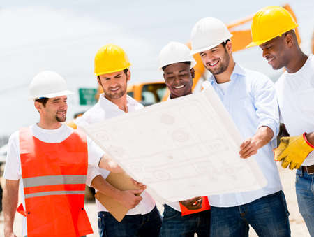 Group of workers at a construction site looking at blueprints