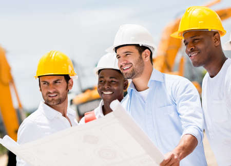 civil engineering: Engineers working on a building site holding a blueprints Stock Photo