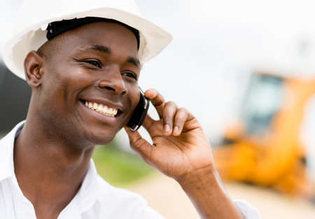 Civil engineer talking on the phone at a construction site photo