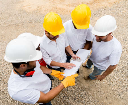 Group of construction workers talking at a building site photo
