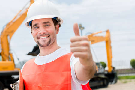 Happy contractor at a building site with thumbs up photo