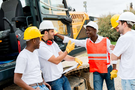 construction safety: Group of workers talking at a building site Stock Photo