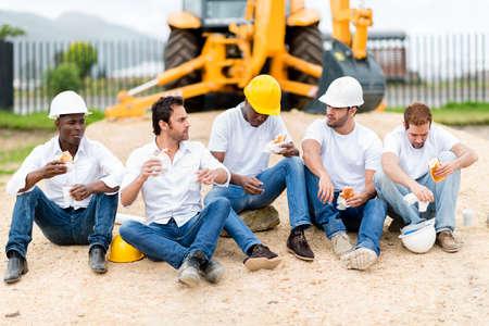 trabajadores: Grupo de trabajadores de la construcci�n en un descanso en una obra de construcci�n Foto de archivo