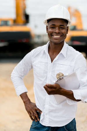 Male architect working at a building site and smiling photo