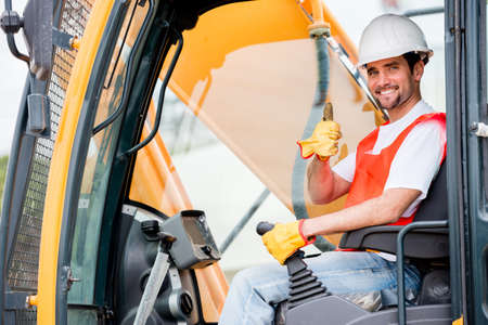 man machine: Crane operator at a construction site looking happy Stock Photo
