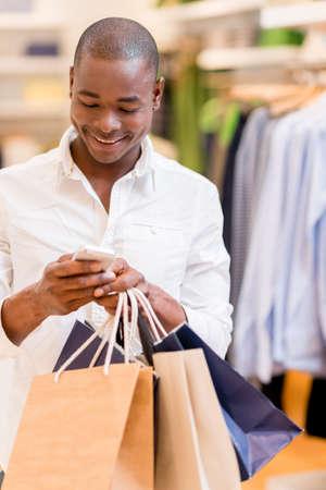 compras compulsivas: Hombre de las compras texting en su teléfono en una tienda Foto de archivo