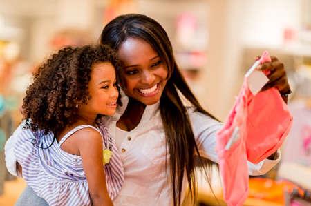 ni�os de compras: Retrato de una madre y su hija de compras para la ropa Foto de archivo