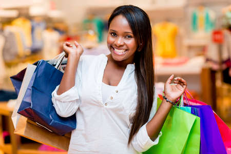 Beautiful shopping woman smiling and holding bags photo
