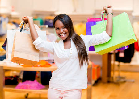 compras compulsivas: Emocionado mujer de compras con sus bolsas con los brazos arriba Foto de archivo