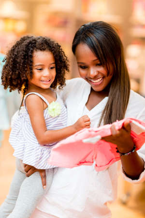 Mother shopping clothes for her daughter at a retail store