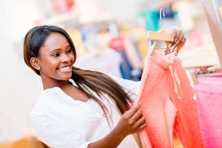 Happy shopping woman looking at clothes at a retail store photo