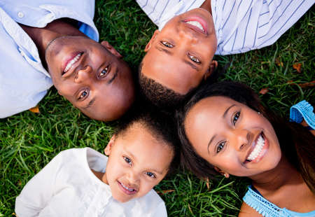Happy family portrait lying on the floor outdoors photo