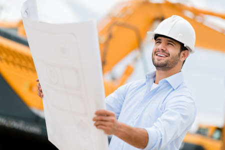 contractors: Architect looking at blueprints in a building site